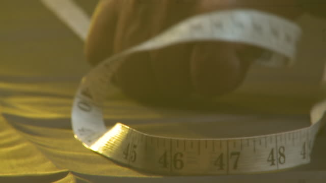 CU TU Shot of man measuring fabric out with tape measure / South Africa