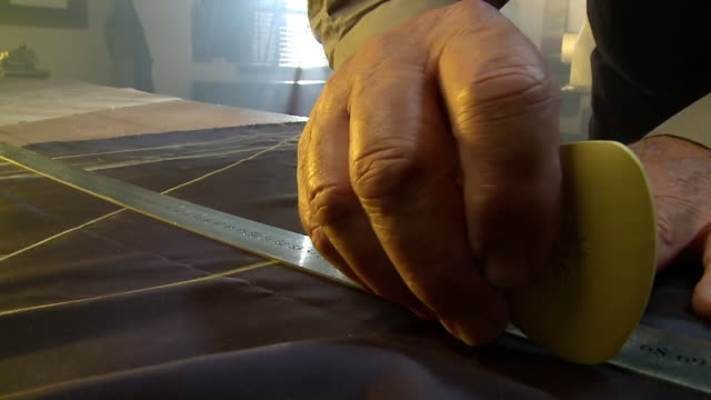 CU Shot of man measuring out fabric with ruler and clover chalk / South Africa