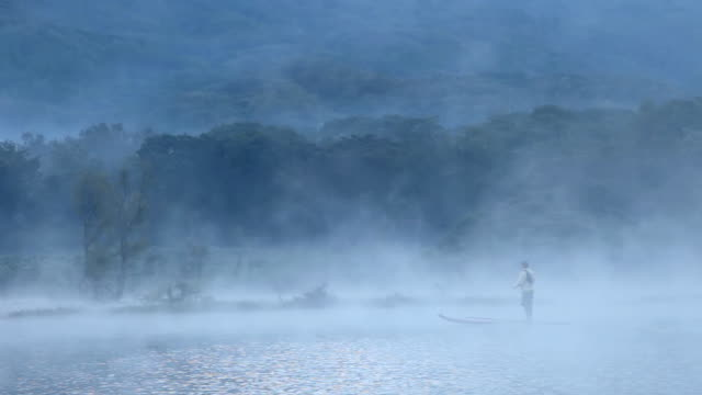 ws shot of man on paddleboard with fly fishing pack and fly rod paddling across misty lake / lake atitlan, guatemala - guatemala stock videos & royalty-free footage