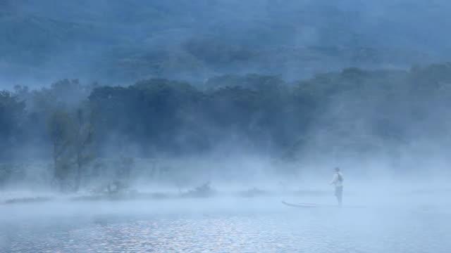 ws shot of man on paddleboard with fly fishing pack and fly rod paddling across misty lake / lake atitlan, guatemala - guatemala stock videos & royalty-free footage