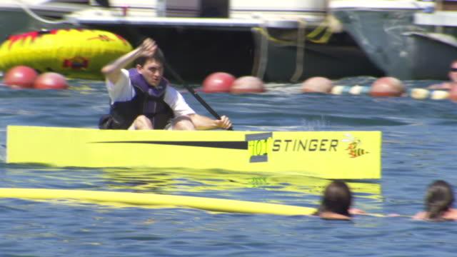 vídeos y material grabado en eventos de stock de ms ts shot of man paddling his yellow cardboard kayak during world championship cardboard boat race / heber springs, arkansas, united states - un solo adolescente