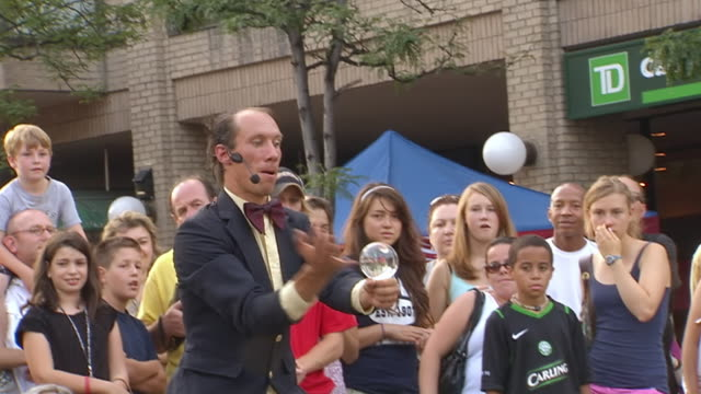 vídeos de stock, filmes e b-roll de ms zo zi shot of man performing contact juggling tricks with crystal ball at busker fest / toronto, ontario, canada - mágico