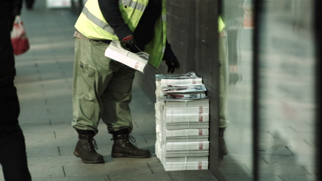ms slo mo shot of man picks up city center newspapers / united kingdom - stack点の映像素材/bロール