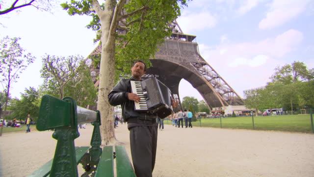 vídeos y material grabado en eventos de stock de ms shot of man playing musical instrument at near eiffel tower / paris, france - acordeonista