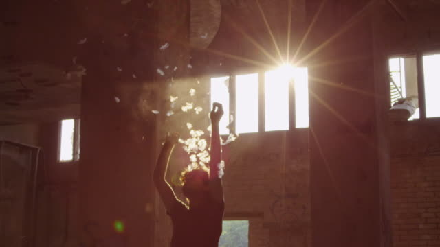 """MS SLO MO Shot of Man popping big white balloon with feathers in it in sunlight in abandoned building / Berlin, Germany"""