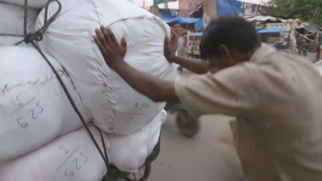 MS POV TS Shot of Man pushes heavily laden cart / New Delhi, India