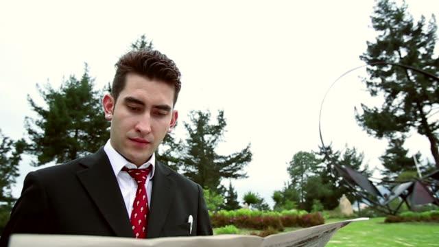 vidéos et rushes de ms tu slo mo shot of man reading newspaper / quito, ecuador - costume complet