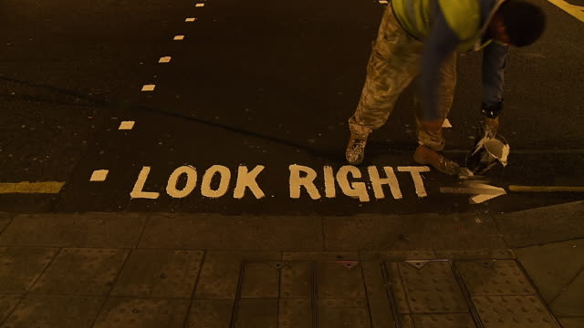 """ms t/l shot of man repainting """"look right' sign on road at night / london, united kingdom  - road sign stock videos & royalty-free footage"""
