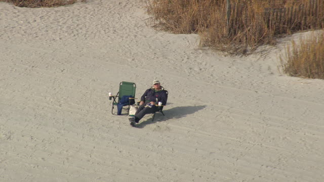 ms aerial shot of man resting near on beach / south carolina, united states - carolina beach stock videos and b-roll footage