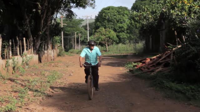 MS Shot of man riding bicycle on village road / Serra Pelada, Para, Brazil