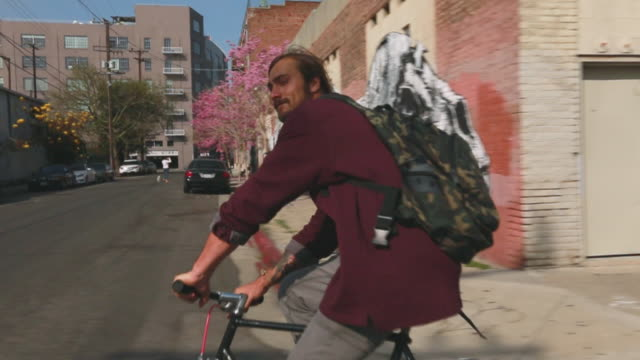 stockvideo's en b-roll-footage met ms slo mo ts shot of man riding bike on city street in / los angeles california united states - mouw