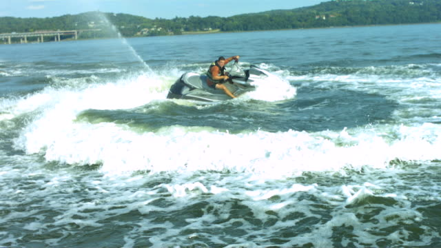 ws slo mo shot of man riding on jet ski in circular motion / new york, united states - acquascooter video stock e b–roll