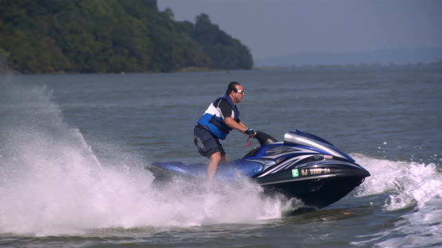 ws ts r/f slo mo shot of man riding on jet ski while jumping several waves / new york, united states - jet ski stock videos & royalty-free footage