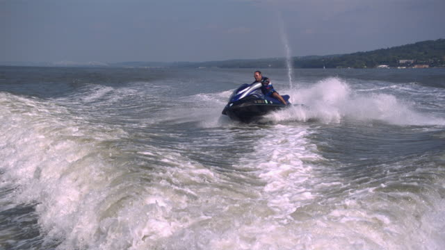 ws ts slo mo shot of man riding on jet ski while jumping waves / new york, united states - one mid adult man only stock videos & royalty-free footage