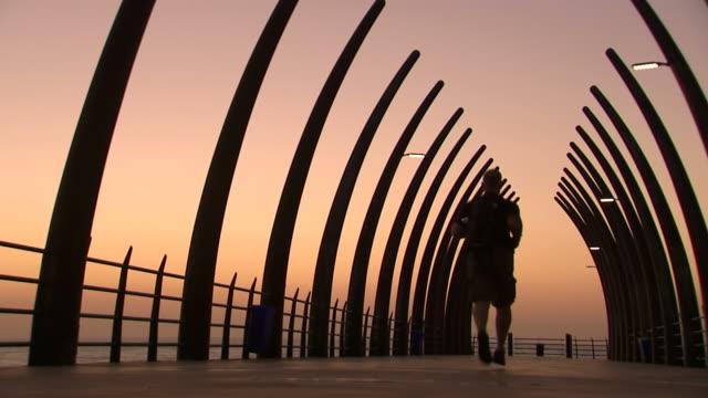 MS LA Shot of Man running down Umhlanga pier at sunset / Kwazulu-Natal, South Africa