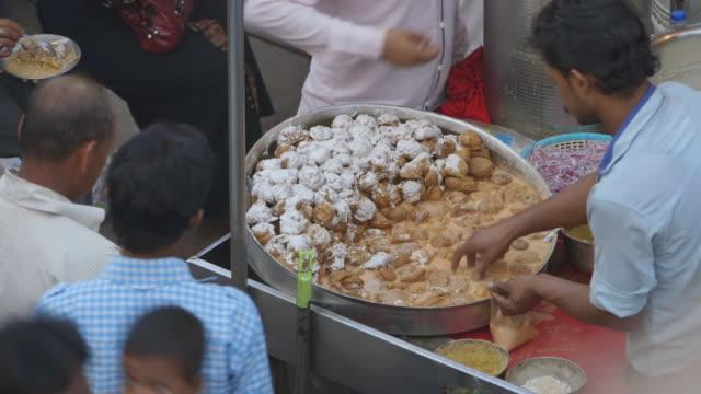 MS HA Shot of man serves portion of food at market / New Delhi, India