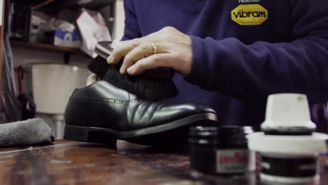 vídeos de stock, filmes e b-roll de shot of man shining a black shoe - classified ad