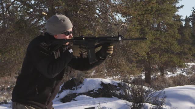 cu slo mo shot of man shoots  ar-15 rifle in winter wood landscape / bend, oregon, united states  - fucile video stock e b–roll