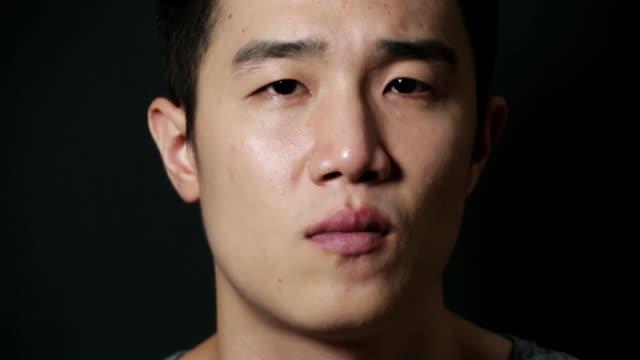 CU Shot of man showing Impassive expression and blinking eyes / Seoul, South Korea