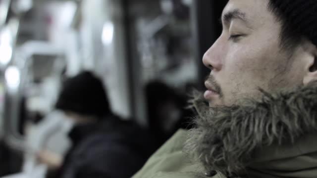 CU Shot of man sleeping in train at night / Shinjuku, Tokyo, Japan