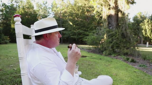 stockvideo's en b-roll-footage met ms shot of man smoking cigar outside his home / st. simons island, georgia, united states - armstoel