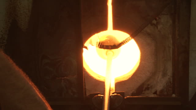 MS ZI Shot of man spins rod to melt in furnace / kauai, hawaii, united states