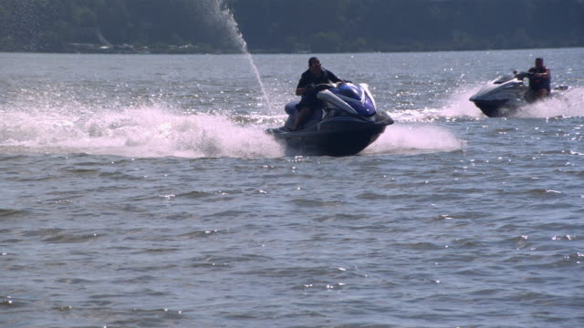 ws ts zo slo mo shot of man standing up on jet ski while jumping on waves / new york, united states - acquascooter video stock e b–roll