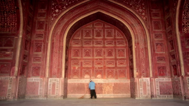 ms shot of man sweeping ground in front of red ornate wall / agra, uttar pradesh, india - uttar pradesh stock videos and b-roll footage