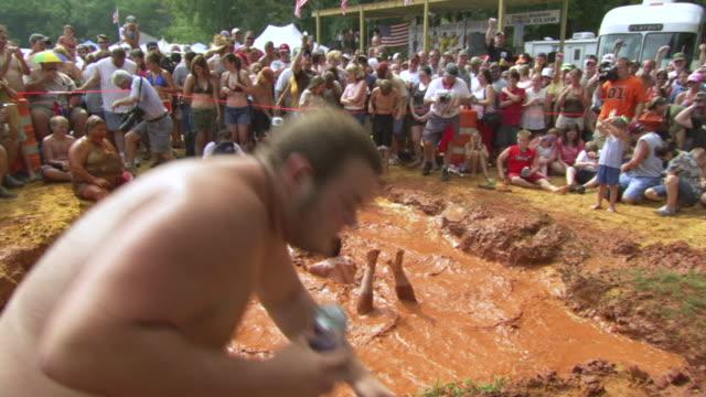 ws ts zi shot of man throwing himself into mud pit making big splash during competition at summer redneck games / dublin, georgia, united states - ヒルビリー点の映像素材/bロール