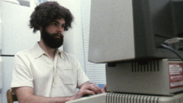 ms shot of man typing on 1980s era apple ii computer / new york , united states - apple computer stock-videos und b-roll-filmmaterial