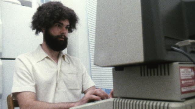 MS Shot of Man typing on 1980s era Apple II computer / New York , United States