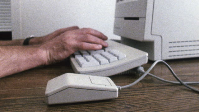 cu shot of man typing on 1980s era mac computer and using mouse / new york , united states - 1980 stock videos and b-roll footage