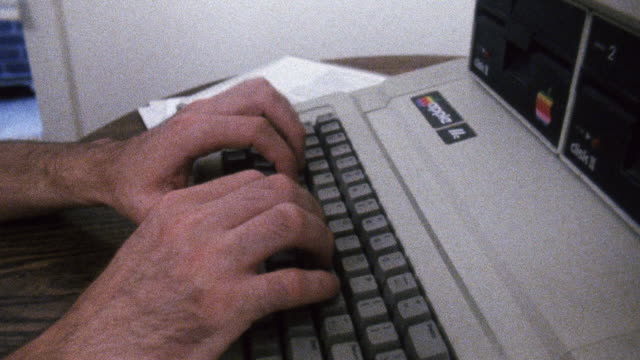 CU TU TD Shot of Man typing on Apple II computer and playing oregon trailr / New York, United States