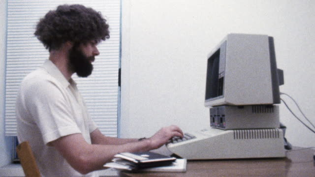 MS Shot of Man typing on Apple II computer / New York, United States