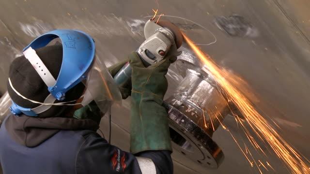 cu pan shot of man using grinder on pressure vessel / johannesburg, gauteng, south africa - ハウテング州点の映像素材/bロール
