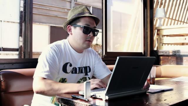 ms shot of man using his laptop at cafe / shonan, kanagawa, japan - 相模湾点の映像素材/bロール
