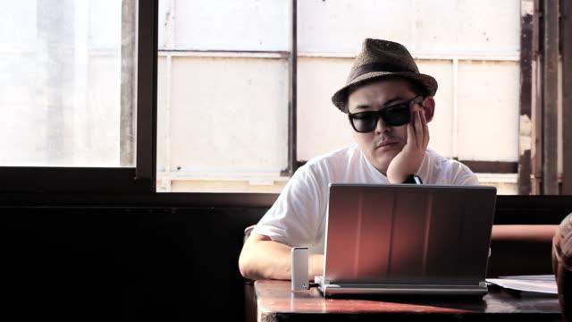MS Shot of man using his laptop at cafe / Shonan, Kanagawa, Japan