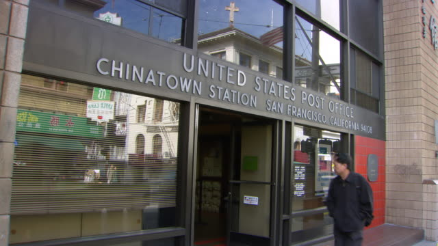 ms shot of man walking by san francisco chinatown station of united states post office / san francisco, california, united states - post office stock videos & royalty-free footage
