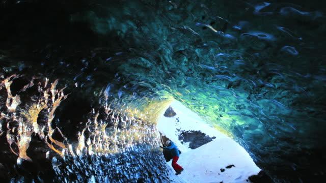 vídeos de stock e filmes b-roll de ws shot of man walking near ice cave at svinaffellsjokull glacier / iceland - islândia