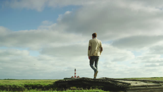 ws la shot of man walking on bridge then on green pastures wit lighthouse in distance / st. peter ording, schleswig holstein, germany  - deutsche nordseeregion stock-videos und b-roll-filmmaterial