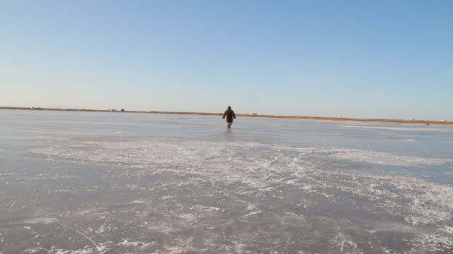 stockvideo's en b-roll-footage met ws shot of man walking on frozen ice / arviat, nunavut, canada - wiese
