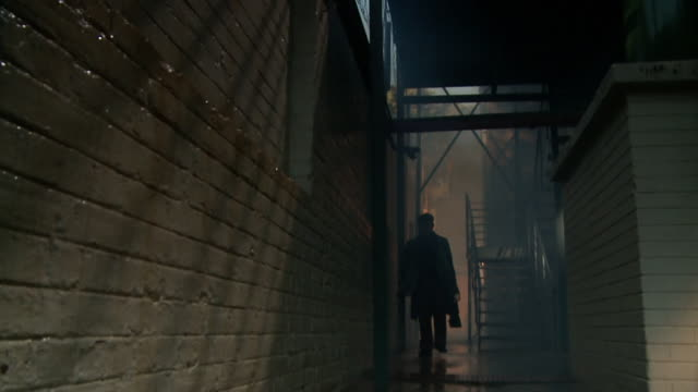 vidéos et rushes de ms shot of man walking through gloomy alley / south africa - sombre