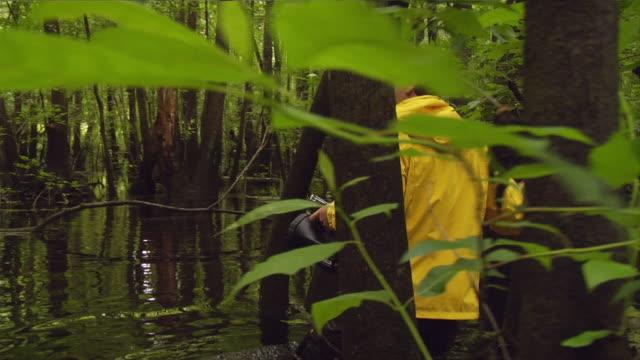 ms ts shot of man walking through swampy water / manteo, north carolina, united states - waterproof clothing stock videos and b-roll footage