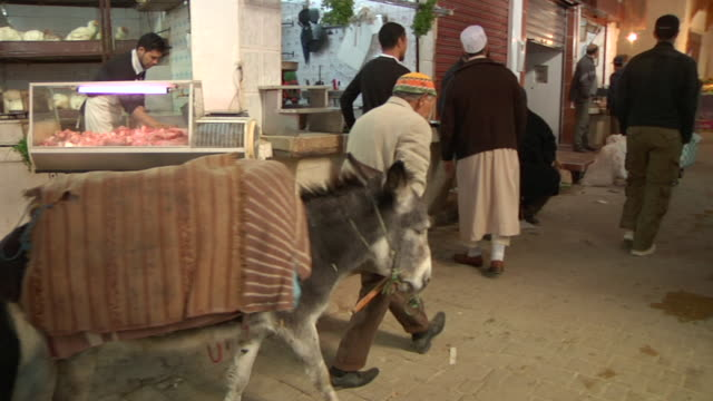 ms pan shot of man walking with donkey through marketplace in downtown / casablanca, centro, morocco - wiese点の映像素材/bロール