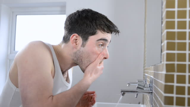 MS Shot of man washing face in bathroom / London, Greater London, United Kingdom