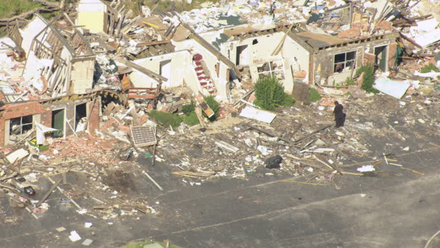 MS AERIAL Shot of man wearing black clothes walking in rubble and ruins of tornado damaged homes / Tuscaloosa, Alabama, United States