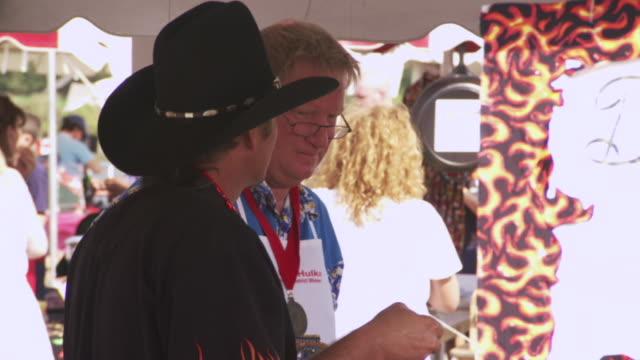 vídeos de stock, filmes e b-roll de ms shot of man wearing black hat tasting some chili during worlds championship chili cook off / omaha, nebraska, united states - campeonato esportivo