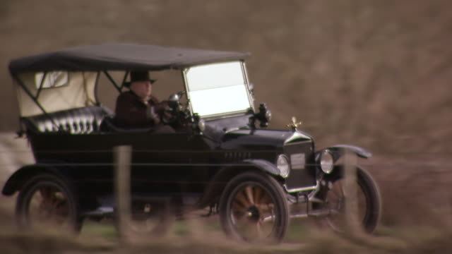 MS TS Shot of man wearing hat drives Ford model T along country road / London, United Kingdom