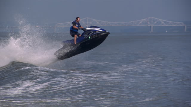 ws ts zo slo mo shot of man wearing sunglasses standing up on jet ski riding in circular motion while jumping waves / new york, united states - giacca di salvataggio video stock e b–roll