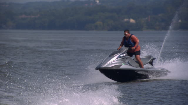 ws ts slo mo shot of man wearing sunglasses standing up on jet ski while jumping several waves / new york, united states - one mid adult man only stock videos & royalty-free footage